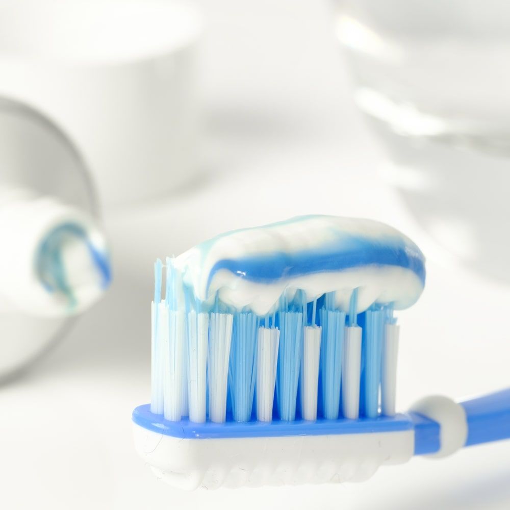 Toothpaste with fluorides and toothbrush.